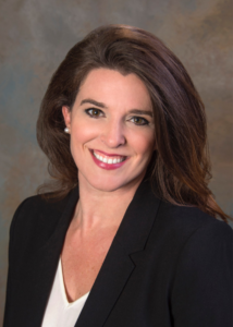 Image of Amanda Tuite wearing a black suit jacket and white shirt smiling at the camera.