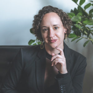 Bethany with short curly hair and her hand resting on her chin wearing a black suit jacket sitting on a couch in front of a light colored wall and a green plant behind her.