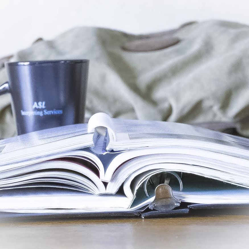 Image of a binder and books sitting on a table with an ASL Interpreting mug sitting behind them.