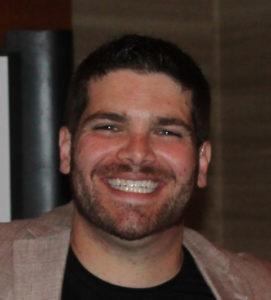 Image of Corey Axelrod wearing a tan blazer and black shirt smiling at the camera.