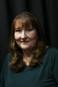 Image of a woman with long brown hair and bangs with a black background.