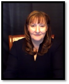 Image of Charlene Crump sitting on a brown chair smiling at the camera.