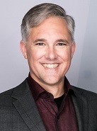 Image of a man with silver hair smiling at the camera.