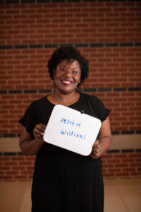 "Image of smiling Black woman holding a marker board that says, ""Felicia Williams""."