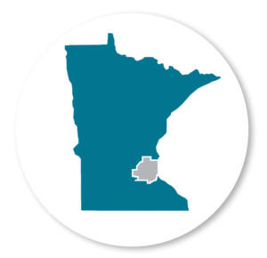 Image of MN State outline on a white background with a gray circle. The seven county metro is outlined in gray, while the remaining image is in teal. The teal color represents Greater MN; the area in which the grant serves.