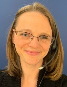 Image of Danielle Meder wearing glasses smiling at the camera with a blue background.
