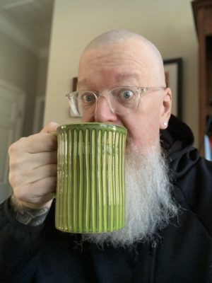 White bald male with a white beard wearing light colored glasses and a black hoodie with a green coffee mug to his lips.