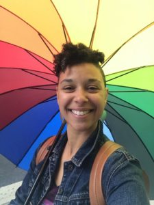 Image of Amy Parsons holding a rainbow umbrella smiling.