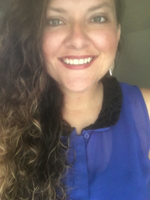 Image of Bree Logan with long curly hair wearing a purple button up tank top and black collar.