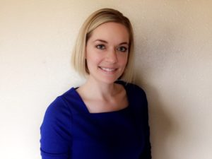 image of Jana standing in front of a cream colored wall wearing a blue shirt and smiling at the camera
