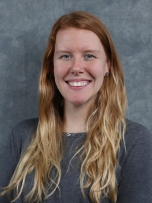 Image of Jenny Smith-Hastings wearing a long sleeve gray shirt standing in front of a gray background. Her smile beaming towards the camera