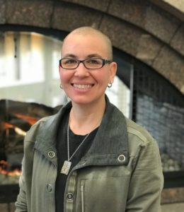 Image of Nic Zapko standing in front of a fireplace smiling at the camera. She is wearing a black shirt and green jacket.