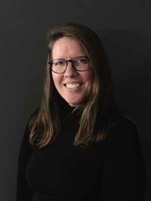 Paula Clark wearing black rimmed glasses and a black turtle neck sitting in front of a black background.