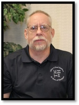 Image of a white male wearing glasses in front of a tan wall. He is wearing a black collared shirt with the MHIT logo on the right side that reads: Office of Deaf Services 25 Years of Excellence.