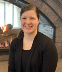 Image of Tarra Grammenos with her hair pulled back smiling wearing a black shirt and long sleeve. She is standing in front of a brick wall and fireplace with the flames of a fire from the fireplace flickering behind her.