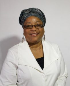 image of Lisa Weems wearing a head wrap, glasses, and dangly earrings, smiling at the camera with a white background