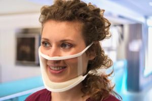 """Woman with curly shoulder length hair wearing the """"clear mask"""". This mask is transparent and shows her entire face. There is a chin padding and piece that sets just slightly above the peak of her nose."""