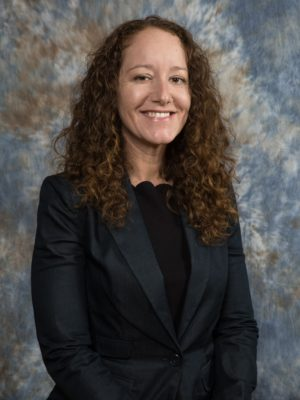 Jasmine, a white female with long curly dark hair, wearing a black shirt and dark grey suit jacket standing smiling.