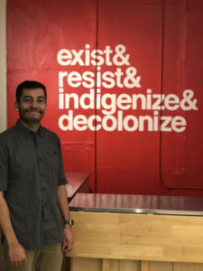 "Image of a latino man smiling. The background behind him is a read wall with white letters that reads, ""exist&resist&indigenize&decolonize"""
